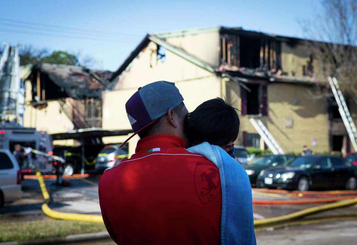 Joey Rodriguez, 4, is held by family friend, Diego, as they look at the apartments where they lived that were destroyed in a Monday morning fire at the complex on S. Gessner Road near Bellaire Blvd., Dec. 24, 2018.
