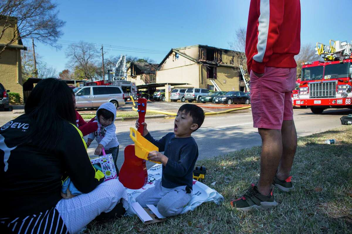 Joey Rodriguez, 4, plays with toys given to them as they wait outside their apartment which was destroyed in a Monday morning fire at the complex on S. Gessner Road near Bellaire Blvd., Dec. 24, 2018.