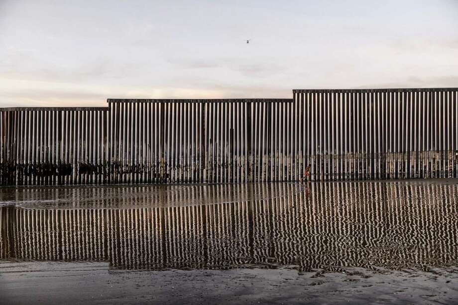 A girl runs towards the sea by the U.S. border fence separating San Diego from Tijuana, Mexico, Sunday, Dec. 23, 2018. Discouraged by the long wait to apply for asylum through official ports of entry, many Central American migrants from recent caravans are choosing to cross the U.S. border wall and hand themselves in to border patrol agents. (AP Photo/Daniel Ochoa de Olza) Photo: Daniel Ochoa De Olza, STR / Associated Press / Copyright 2018 The Associated Press. All rights reserved