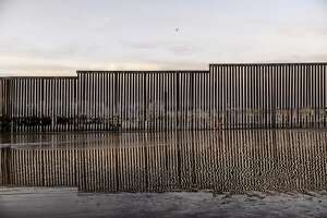 A girl runs towards the sea by the U.S. border fence separating San Diego from Tijuana, Mexico, Sunday, Dec. 23, 2018. Discouraged by the long wait to apply for asylum through official ports of entry, many Central American migrants from recent caravans are choosing to cross the U.S. border wall and hand themselves in to border patrol agents. (AP Photo/Daniel Ochoa de Olza)