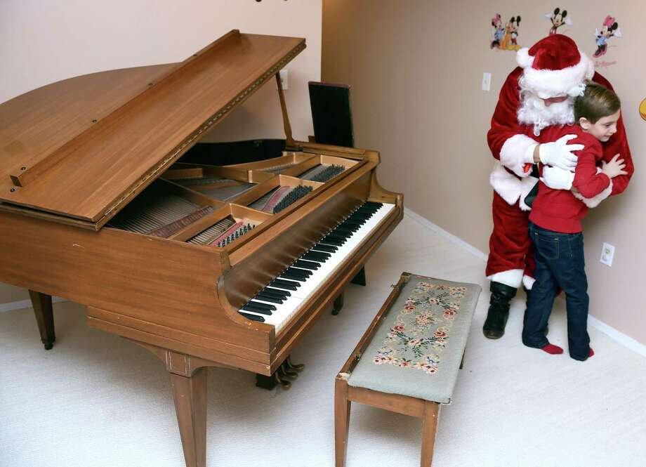 Alexander Stamboulidis, 9, thanks Santa Claus for the delivery of his Christmas wish, a baby grand piano, to his home in North Haven on December 24, 2018. Michael Storz, president of the Chapel Haven Schleifer Center, filled in for Santa Claus. Photo: Arnold Gold / Hearst Connecticut Media / New Haven Register