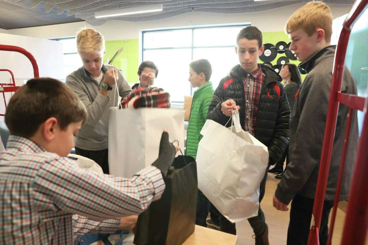 Eastern Middle School student Luke McQuillan, in black jacket, returned to Yale New Haven Hospital, where he had once received treatment for brain cancer, with his friends and family to donate $16,000 in gifts to teens at the hospital receiving treatment.