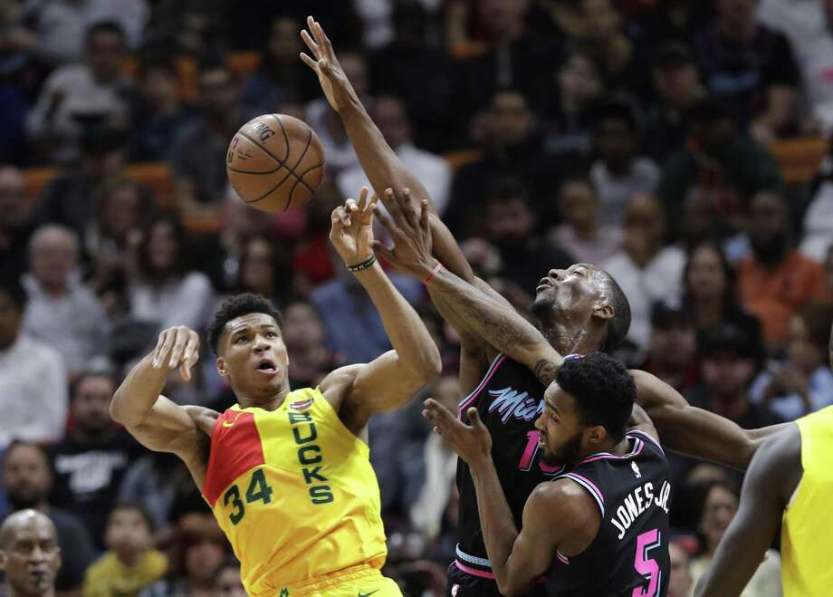 In this Dec. 22, 2018, file photo, Milwaukee Bucks forward Giannis Antetokounmpo (34) passes as Miami Heat center Bam Adebayo, center, and forward Derrick Jones Jr. (5) defend during the first half of an NBA basketball game in Miami. On Tuesday, Dec. 25, Antetokounmpo and the Bucks visit the New York Knicks as one of five games on the NBAs holiday schedule. Photo: Lynne Sladky, STF / Associated Press / Copyright 2018 The Associated Press. All rights reserved.