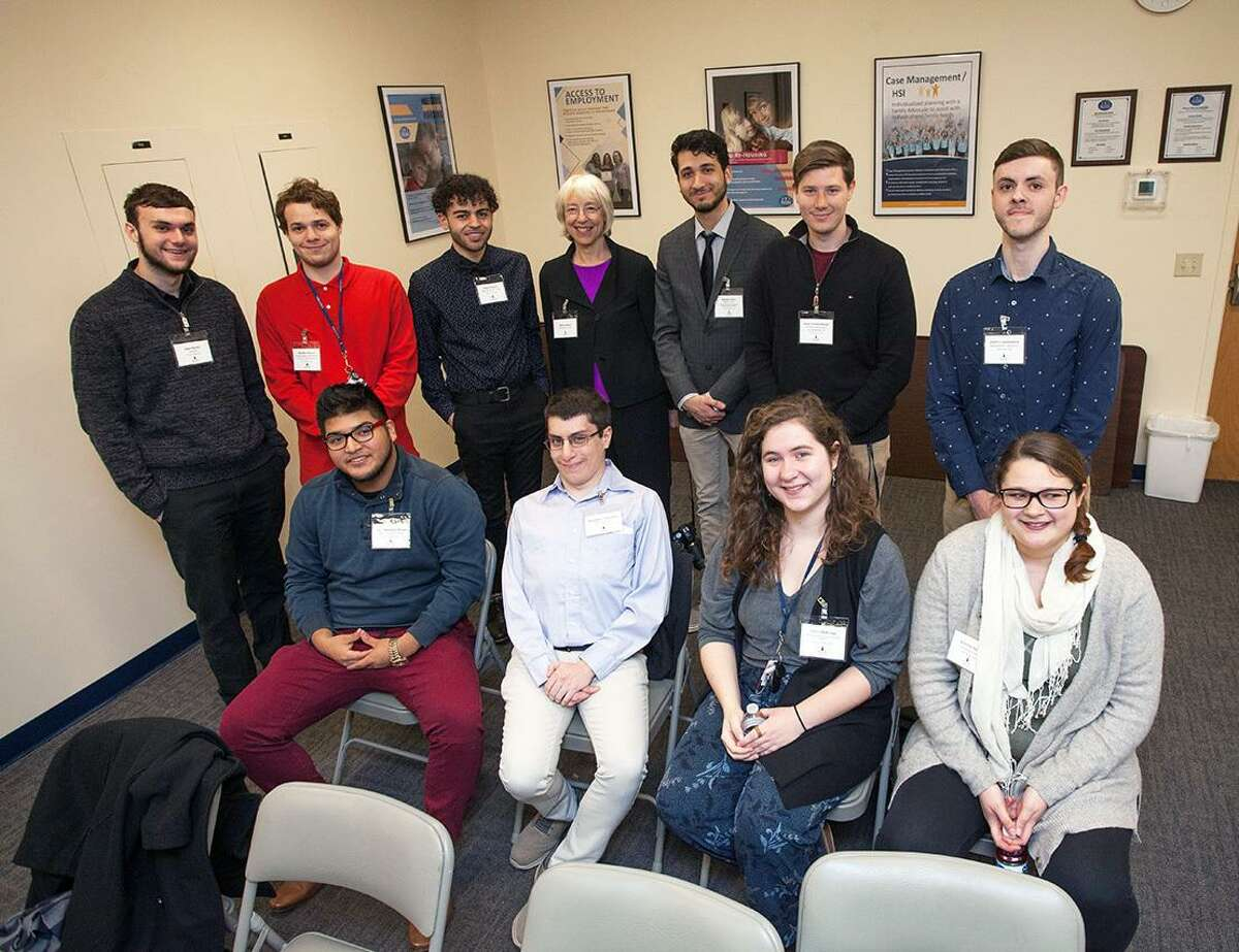 Eastern Connecticut State University Design Group students and Professor Terry Lennox, middle, back row, stand before several of their final poster designs