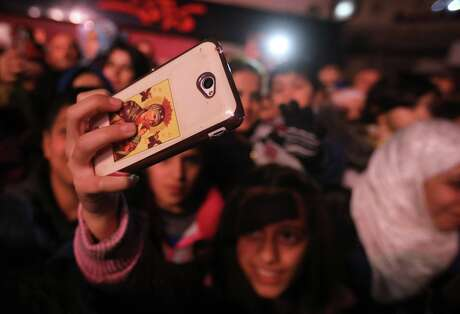 A young woman takes a picture with her smart-phone as people gather in the centre of the Syrian capital Damascus to watch the lighting of a giant Christmas tree on December 23, 2018. (Photo by LOUAI BESHARA / AFP)LOUAI BESHARA/AFP/Getty Images