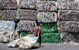 TOPSHOT - A worker walks in front of packed recyclable plastic bottles at La Sylvia recycling center in Barva, province of Heredia, Costa Rica on June 20, 2018. - Costa Rica discards 564 tons of plastic per day of which only 14 are recycled, according to the Ministry of Health's Office of Environmental Health in charge of waste management in the country. Since April 2018, a program seeks to stimulate recycling by giving value to waste through the exchange of it for a virtual currency that allows users to make purchases at stores linked with the initiative. (Photo by EZEQUIEL BECERRA / AFP)EZEQUIEL BECERRA/AFP/Getty Images
