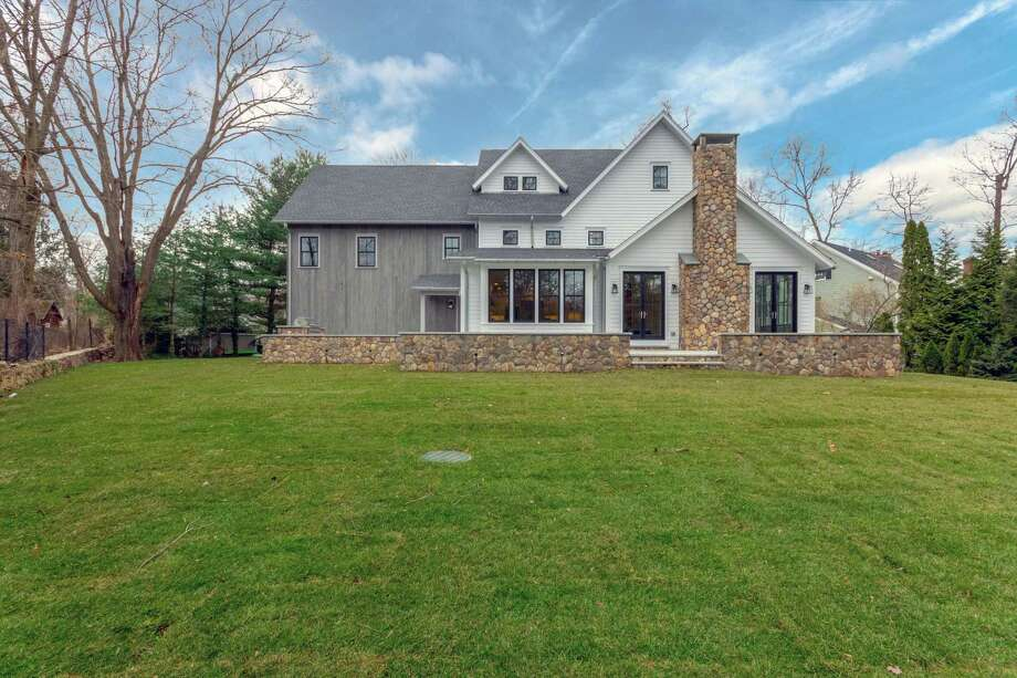 This 6,679-square-foot home sits on a level property of almost half an acre with a large wrap-around granite deck and built-in gas grill. / Listing Style LLC