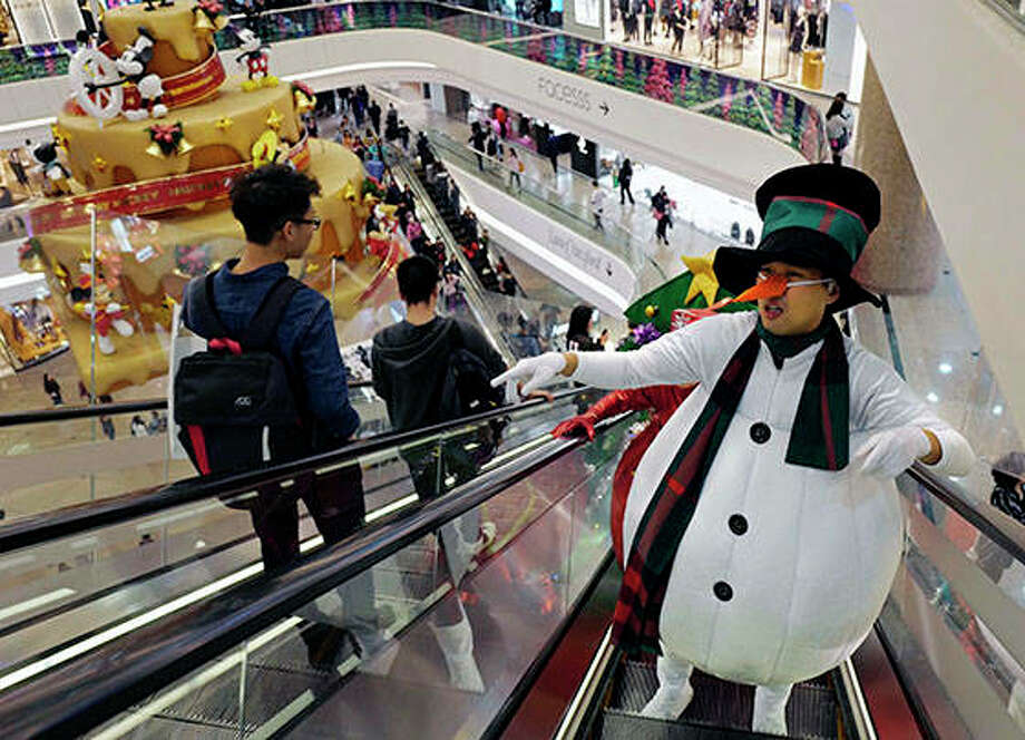 Promoters dressed as Christmas characters get on an escalator at a shopping mall as the territory prepares to celebrate the Christmas holidays, in Hong Kong Monday, Dec. 24, 2018. (AP Photo/Vincent Yu)