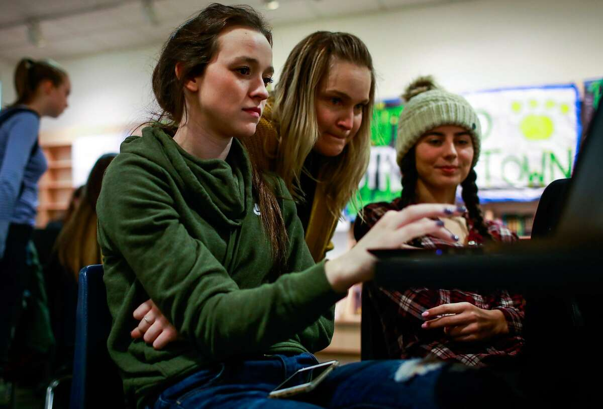 Paradise evacuee Faith Brown (left) gets help from teacher Anne Stearns (center) as she works on her college essays at a makeshift classroom in the Chico Mall where Pardise high school students are temporarily attending school in Chico, California, on Wednesday, Dec. 5, 2018.