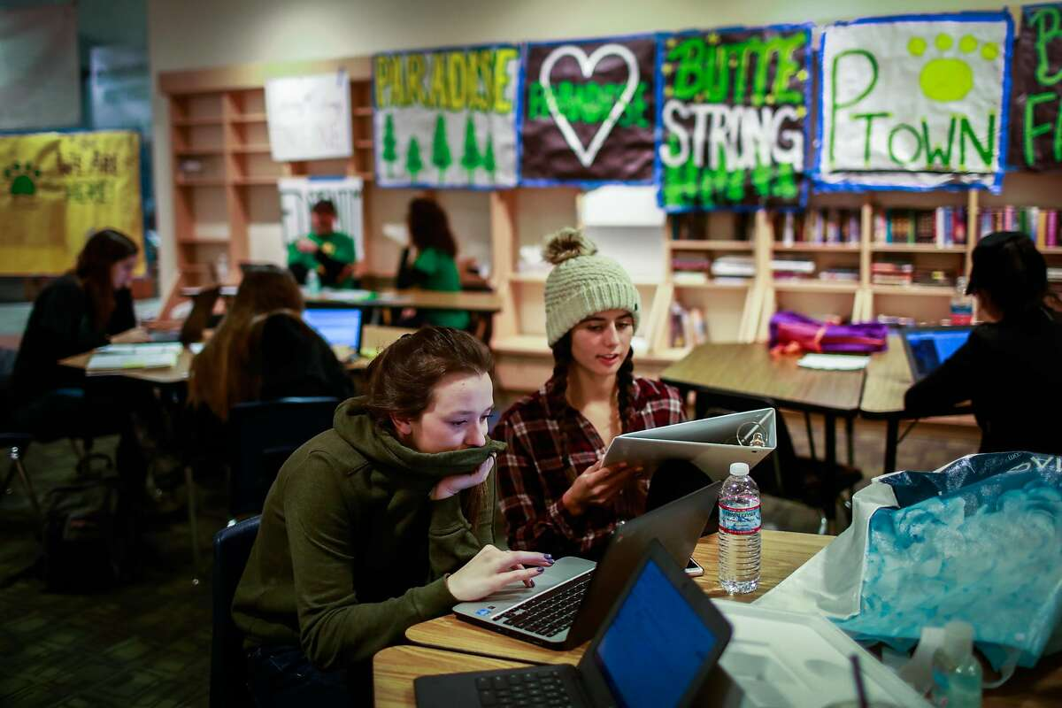 Paradise evacuee Faith Brown (left) works on her college essays alongside friend Kaylee Suniga (right) at a makeshift classroom in the Chico Mall where Pardise high school students are temporarily attending school in Chico, California, on Wednesday, Dec. 5, 2018.