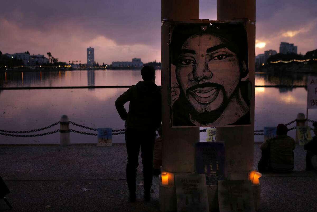 A poster with a drawing of Oscar Grant is hung above a memorial for victims of police shootings at the colonnade at Lake Merritt on Sunday. Several groups gathered to remember victims of police shootings and find alternatives to the violent protests that plagued Oakland, Calif., Sunday evening, November 30, 2014. A group of about 70 people gathered at the pergola and colonnade at Lake Merritt for the Vigil for Fallen Angels, and a similar number joined for a Community Prayer Vigil at Beebe Memorial Cathedral.