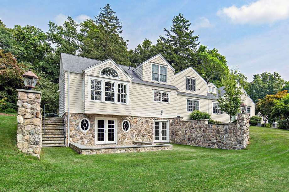 The stone and clapboard colonial farmhouse at 75 Steep Hill Road sits on a level and sloping property of 7.5 acres that serves as a hobby farm.