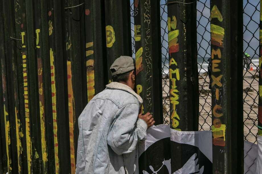 A man looks through the border wall to the US side, in Tijuana, Mexico on April 29. Migrants from Central America wanting to gain asylum in the United States are motivated by purely practical reasons. Photo: MEGHAN DHALIWAL /NYT / NYTNS