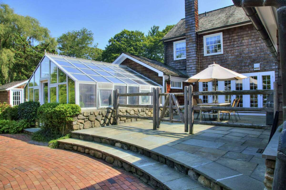 This property has a couple of slate patios and a greenhouse-like solarium or sunroom.