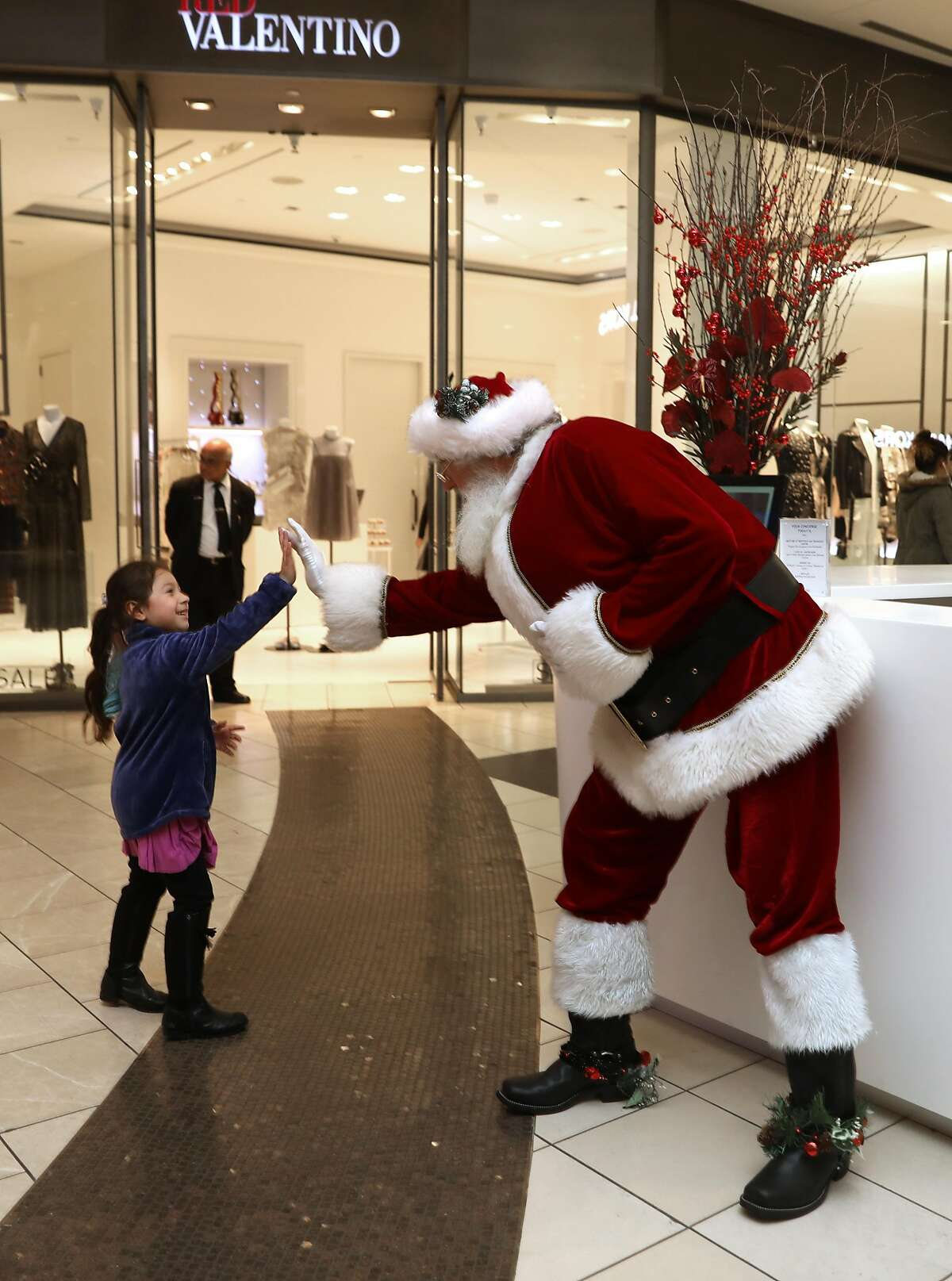William Hackett greets Emily Ek at the Westfield San Francisco Centre. The mall encourages shoppers to use their own phones or cameras to take photos with