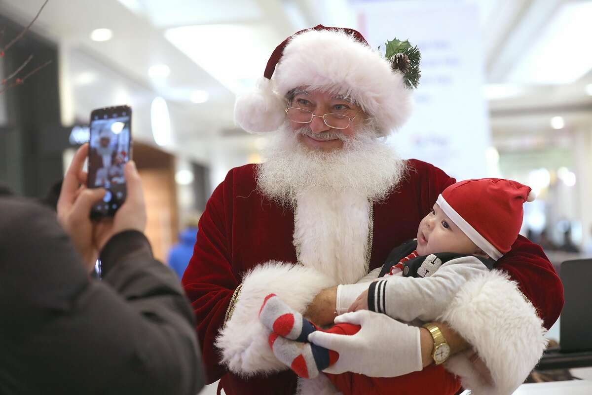Wesley Gong has a photo taken with Santa William Hackett at Westfield San Francisco Centre.