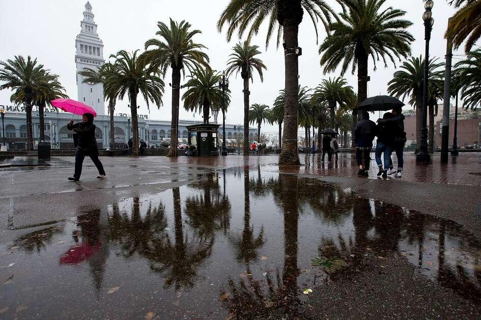San Francisco, CA: Pedestrians endure the rainy weather on Christmas Eve outside Embarcadero Center. December 24, 2018. Photo by Lisa Hornak