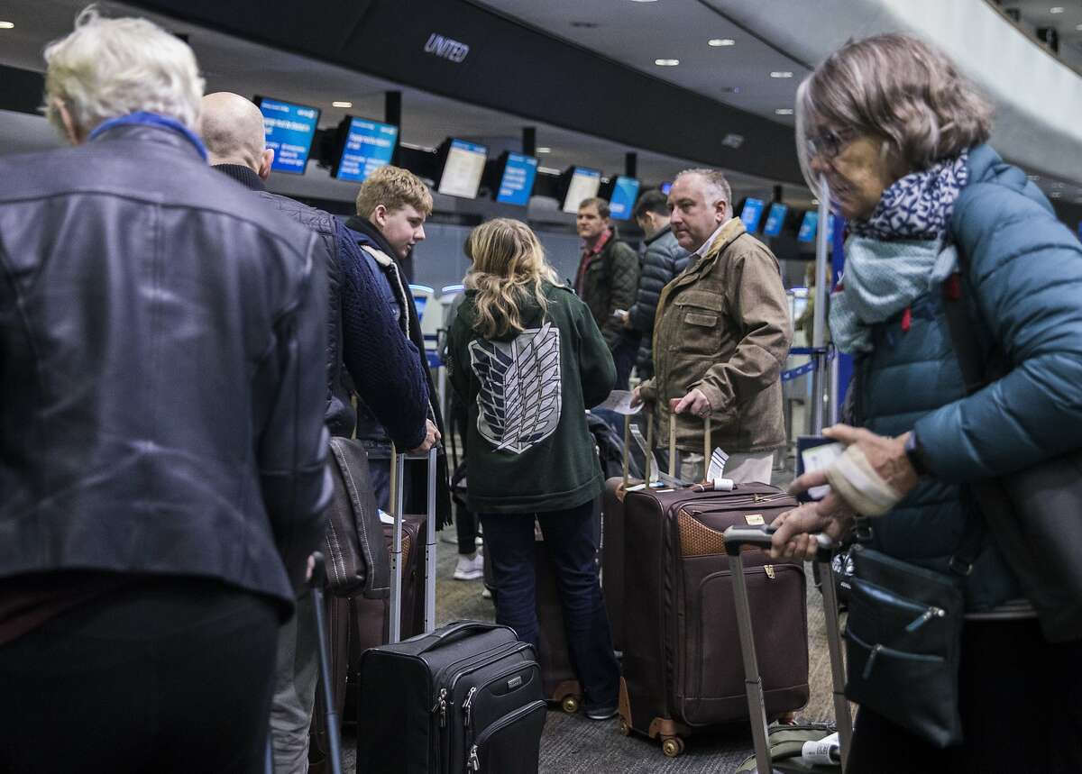 Passengers stand in long lines near the ticketing booth before catching their flights from the San Francisco International Airport in San Francisco on Wednesday, Dec. 19, 2018. Cal/OSHA said Monday it will be conducting interviews with employees of Gladiator Rooter & Plumbing while checking its safety records. On Saturday afternoon, two of its employees apparently became overwhelmed by exhaust from a gas-powered piece of equipment they were using while working in underground tunnels beneath the Gate Gourmet catering facility.
