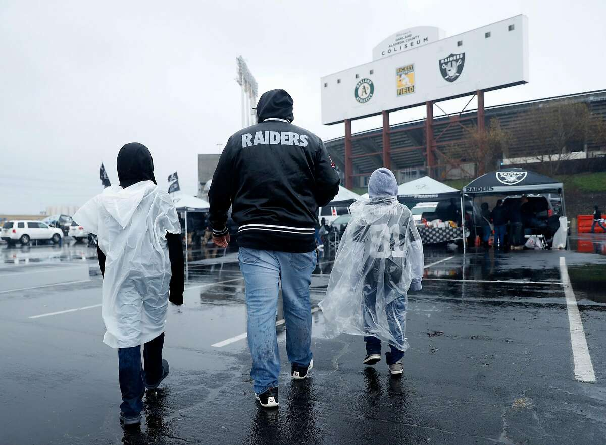 Oakland Raiders' fan Marco Cortez of Concord and his sons, Danny, 7, and Adrian, 10, walk toward what might be the final Raiders' game at Oakland Coliseum in Oakland, Calif. on Monday, December 24, 2018.