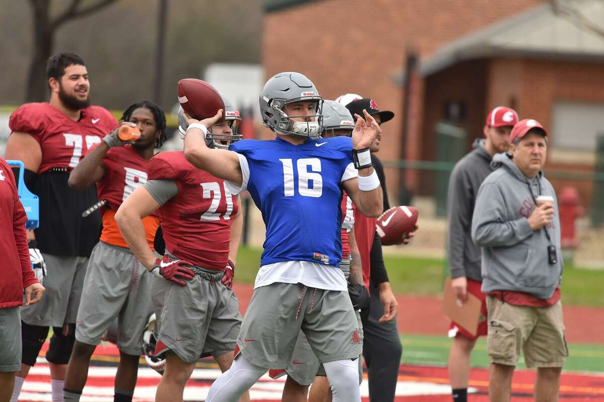 Washington St. quarterback Gardner Minshew throws downfield while practicing Monday at the University of the Incarnate Word for the upcoming Alamo Bowl. Head Coach Mike Leach watches at right.