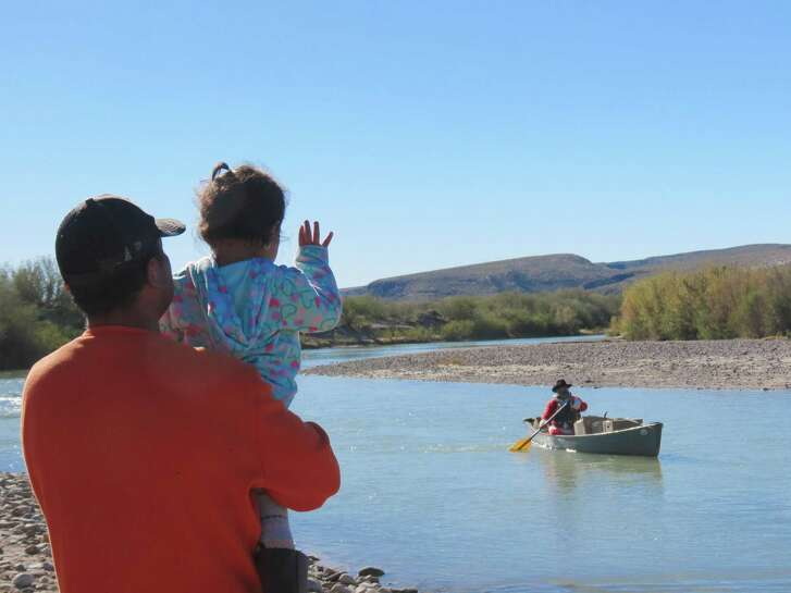"Camila Uresta waves as ""Santa"" Marcos Paredes floats to the shore of Boquillas del Carmen, a small village located in Big Bend National Park."