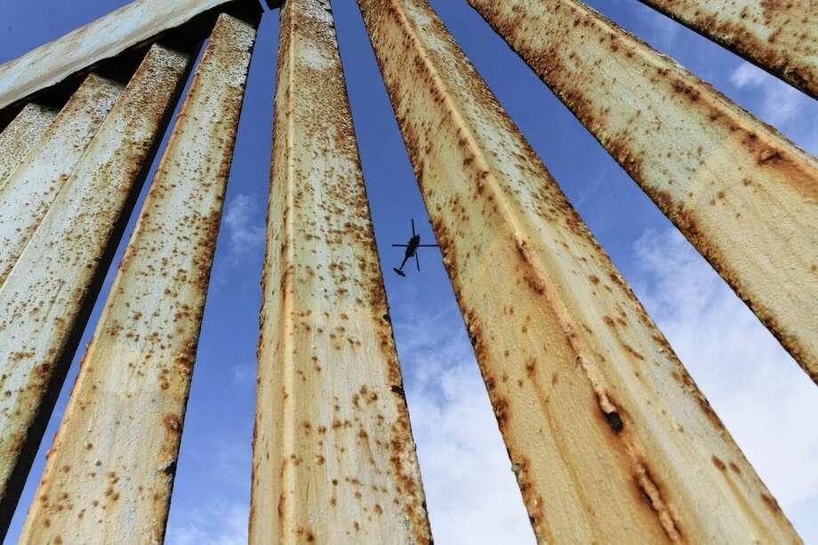 Un helicóptero monitorea la cerca fronteriza de Estados Unidos, visto desde Tijuana, México, el domingo 23 de diciembre de 2018. Photo: Daniel Ochoa De Olza /Associated Press / Copyright 2018 The Associated Press. All rights reserved
