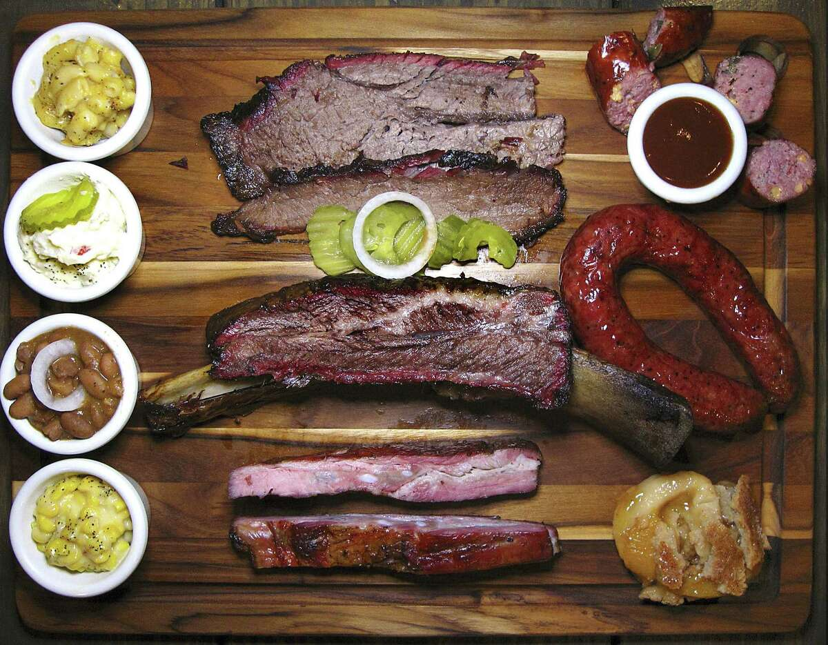 Barbecue and sides from The Original Black's Barbecue in New Braunfels. Clockwise from top left: mac and cheese, brisket, jalapeño-cheese sausage, beef sausage, peach cobbler, pork spare ribs, creamed corn, pinto beans, potato salad and a beef rib.