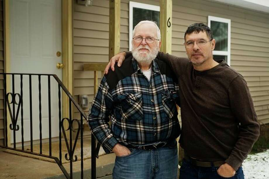 Rich Campbell, left, and Ed Ball, right, pose for a portrait together in front of the Sanford apartment building they both live in on Saturday. In 1970, Campbell was Ball's 'big brother' as part of the Big Brothers program in their hometown of Flint. The two reunited this year and Ball has welcomed Campbell into his family. (Katy Kildee/kkildee@mdn.net)