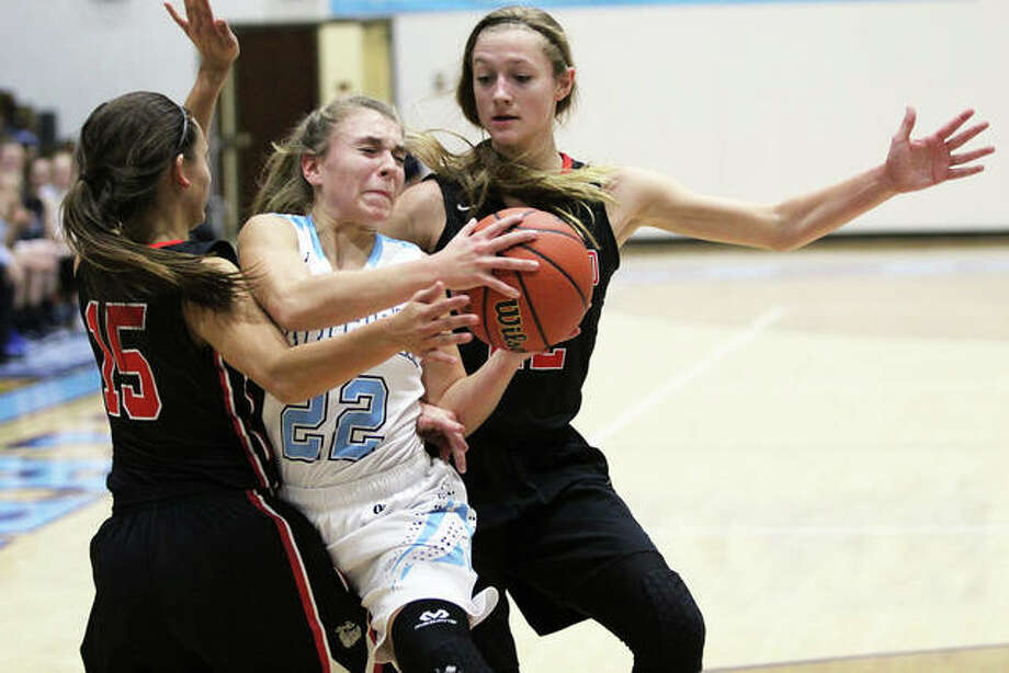 Jersey's Clare Breden (middle) splits Highland defenders Megan Kronk (left) and Ashlyn Klucker during a Dec. 3 game in Jerseyville. The Panthers will be back home for holiday play as host of the Jersey Tourney that tips off Thursday at Havens Gym. Photo: Greg Shashack / The Telegraph