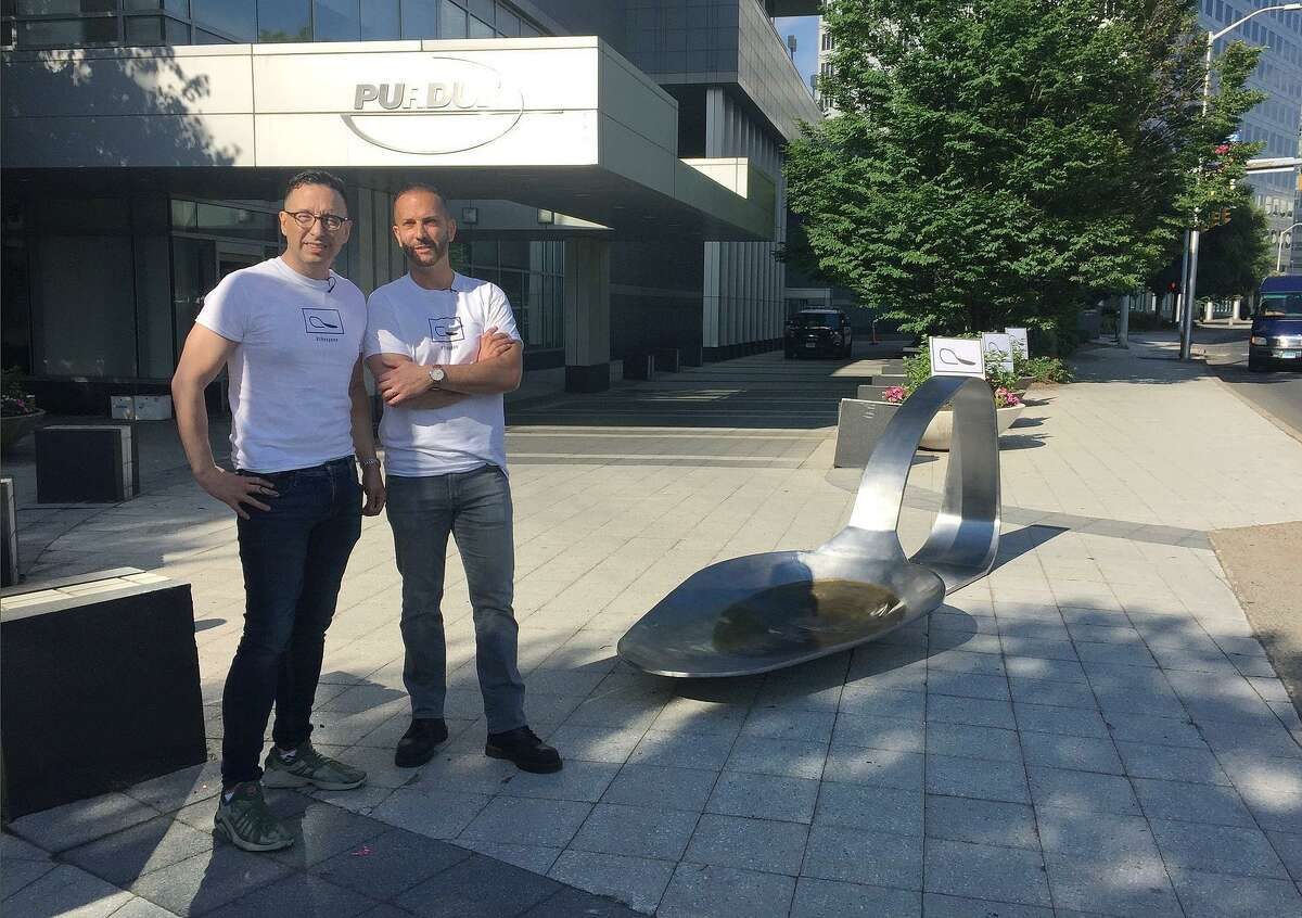 Art gallery owner Luis Alvarez, left, and sculptor Domenic Esposito stand with an 800-pound sculpture of a bent, burnt heroin spoon placed in front of the Purdue Pharma headquarters in June. Alvarez plans to close his downtown Stamford gallery in January.