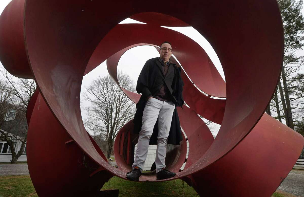 Fernando Alvarez, owner of Alvarez Gallery in Stamford, with the 30-foot-long, 12,000-pound sculpture by artist Charles O'Perry he recently acquired. The sculpture had been a public art installation at the Stamford Town Center mall and was removed and abandoned for a decade. Alvarez plans to close his downtown Stamford gallery in January.