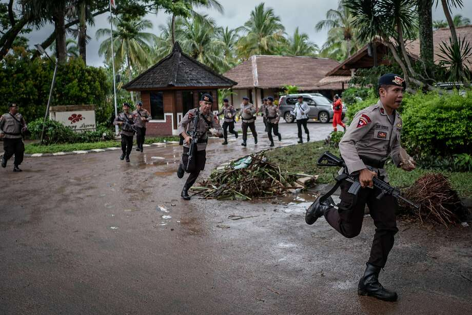 Indonesian police run from a resort they had been searching after rumors of a new tsunami spread across the Tanjung Lesung in the Banten province. Hundreds were killed in the Saturday night tsunami. Photo: Ulet Ifansasti / Getty Images