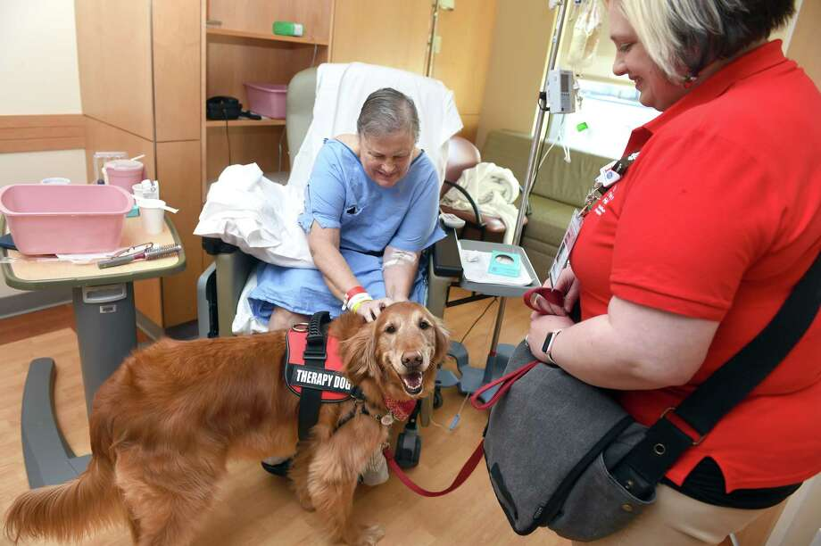Valerie DeMarco (right) of Hamden and her golden retriever service dog, Gunther, spend some time with Karen Joly of Norwich during a visit to Smilow Cancer Hospital in New Haven on December 25, 2018. Photo: Arnold Gold, Hearst Connecticut Media / New Haven Register