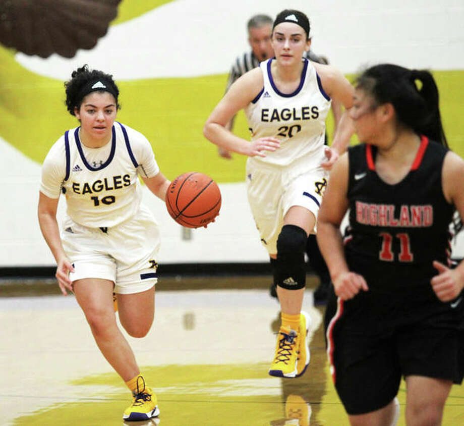 CM's Kourtland Tyus (left) pushes the ball upcourt while teammate Anna Hall follows the play and Highland's Emmy Nyquist (right) retreats on defense during an Eagles win last Thursday in Bethalto. CM takes a 14-0 record and No. 5 seed to the State Farm Classic in Bloomington/Normal. Photo: Greg Shashack / The Telegraph