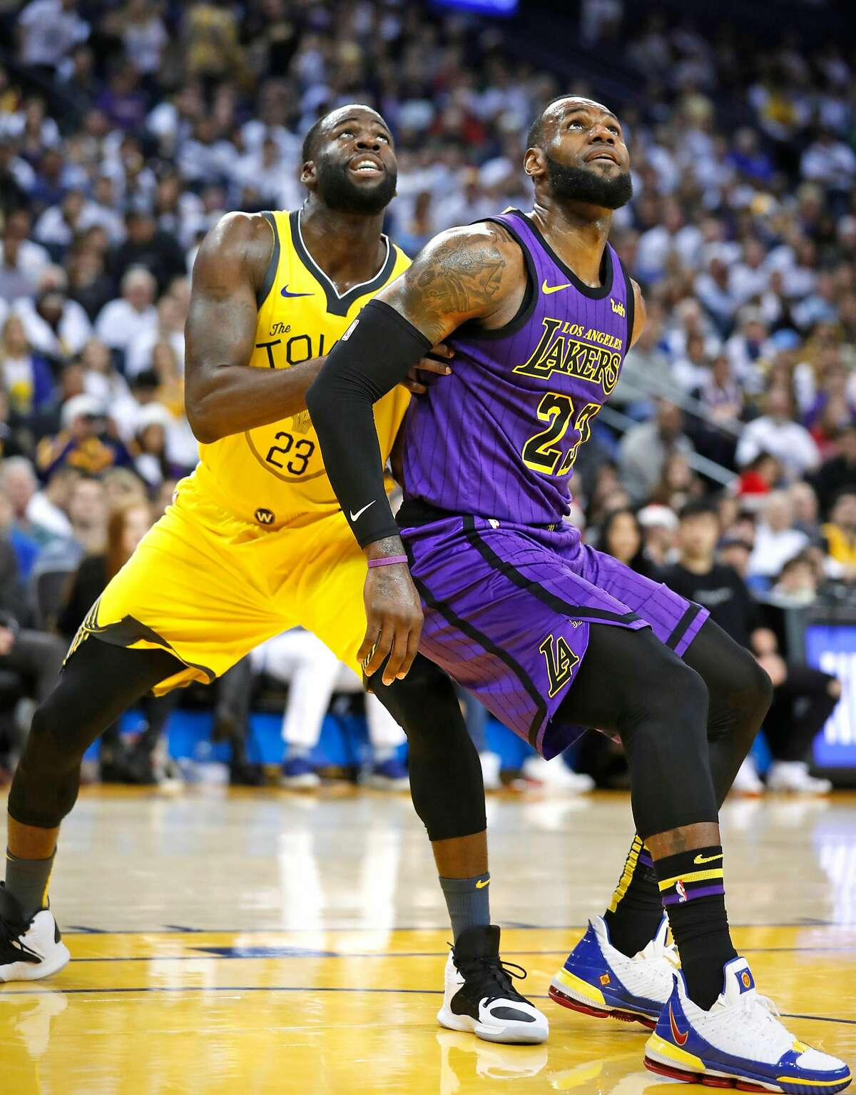 Los Angeles Lakers' LeBron James and Golden State Warriors' Draymond Green vie fro rebound position in 2nd quarter during NBA game at Oracle Arena in Oakland, Calif. on Tuesday, December 25, 2018.