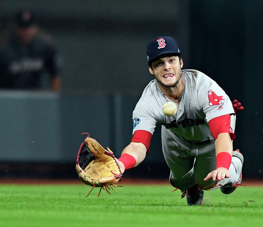 FILE - In this Oct. 17, 2018, file photo, Boston Red Sox' Andrew Benintendi makes a diving catch with the bases loaded for the final out in the ninth inning against the Houston Astros in Game 4 of the American League Championship Series in Houston. The Red Sox defeated the Astros 8-6 to take a 3-1 lead in the series. (Christopher Evans/The Boston Herald via AP, File) Photo: Christopher Evans / The Boston Herald