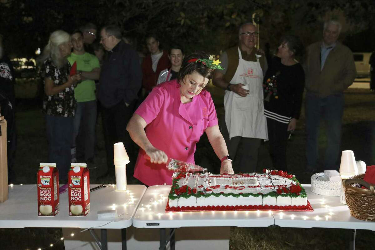 Joan Cheever cuts a cake in her honor during a gathering at Maverick Park, Tuesday, Dec. 25, 2018. After 13 years of providing hot dinners for the homeless, Cheever ended her volunteer service at Maverick Park. A trained chef, author and documentary filmmaker, Cheever is a vocal advocate for the homeless as a writer and lawyer. She said The Chow Train itself, which also travels to disaster scenes to help the