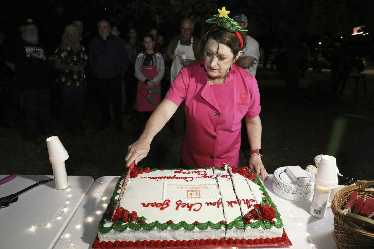 Joan Cheever cuts a cake in her honor during a gathering at Maverick Park, Tuesday, Dec. 25, 2018. After 13 years of providing hot dinners for the homeless, Joan Cheever ended her volunteer service at Maverick Park. A trained chef, author and documentary filmmaker, Cheever is a vocal advocate for the homeless as a writer and lawyer. She said The Chow Train itself, which also travels to disaster scenes to help the