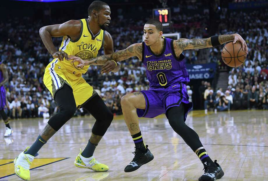 OAKLAND, CA - DECEMBER 25:  Kyle Kuzma #0 of the Los Angeles Lakers dribbles the ball while being closely guarded by Kevin Durant #35 of the Golden State Warriors during the first half of their NBA Basketball game at ORACLE Arena on December 25, 2018 in Oakland, California. NOTE TO USER: User expressly acknowledges and agrees that, by downloading and or using this photograph, User is consenting to the terms and conditions of the Getty Images License Agreement.  (Photo by Thearon W. Henderson/Getty Images) Photo: Thearon W. Henderson / 2018 Getty Images