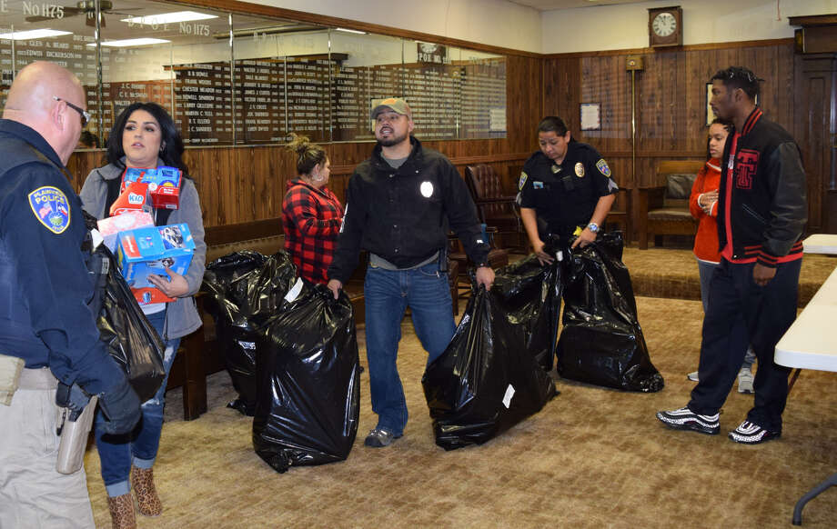 Plainview Police Department officers, dispatchers and their families spent Friday morning loading gifts to deliver to local kids for the department's annual Christmas With Cops program. Photo: Ellysa Harris/Plainview Herald