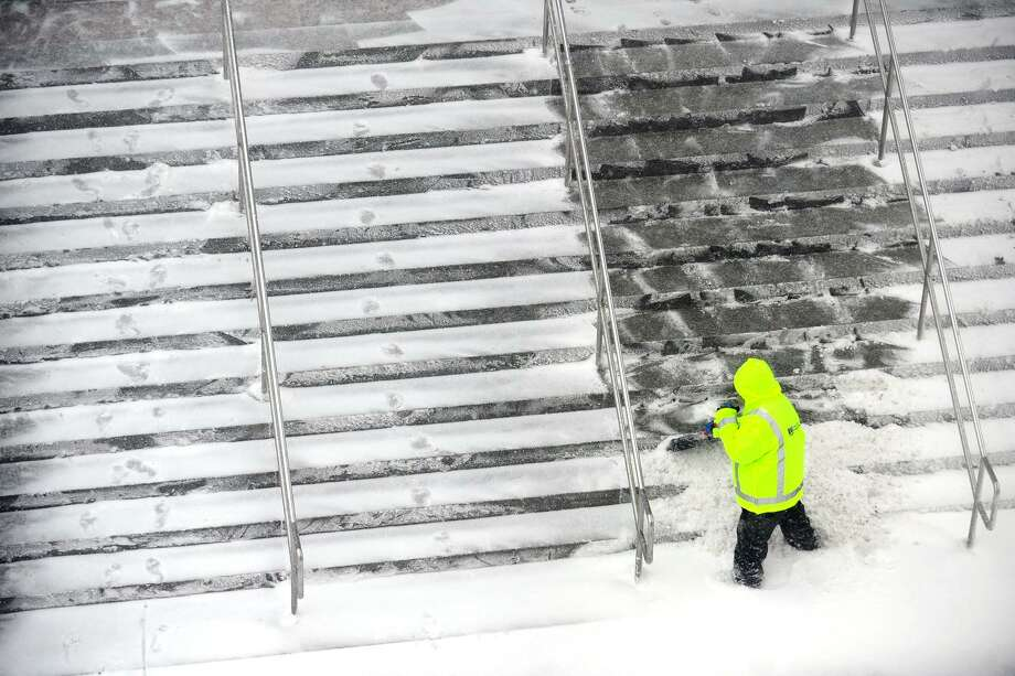 A man shovels snow off stairs outside the Stamford Train Station in downtown Stamford, Conn. on Thursday, Jan. 4, 2018. Snow began early Thursday morning and is continuing throughout the day, coupled with heavy winds and low visibility. Photo: Michael Cummo / Hearst Connecticut Media / Stamford Advocate