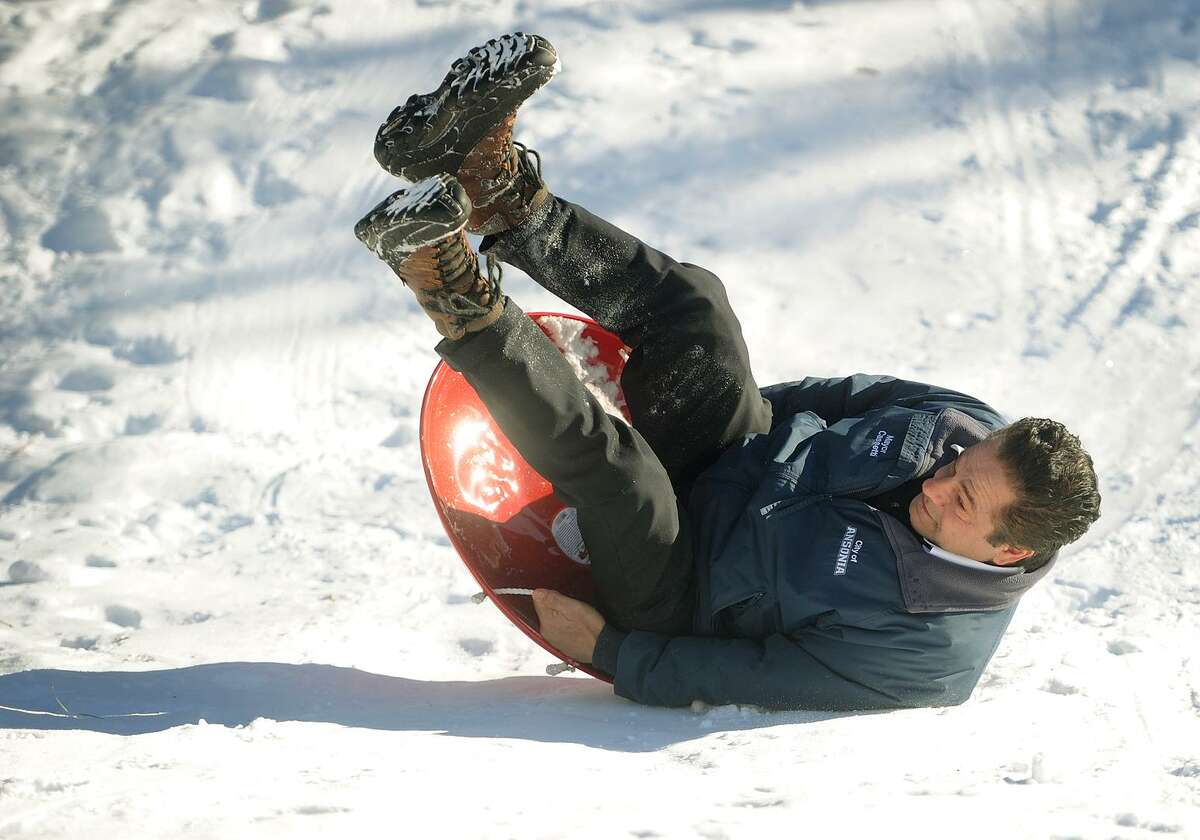 Ansonia Mayor David Cassetti takes a tumble as he takes a sled ride during the grand opening of the new winter playground at Linett Park on Crowley Street in Ansonia, Conn. on Sunday, January 7, 2018.