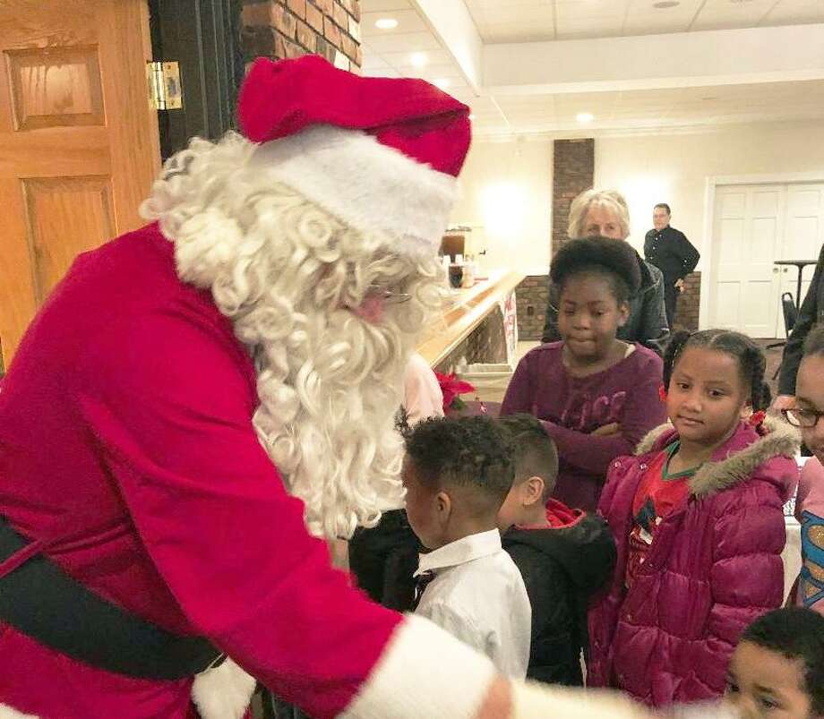 Members of the South Fire District IAFF Local 3918, Connecticut Valley Hospital Police and Middletown Elks Lodge 771 spread joy throughout the city during its annual Adopt-A-Family program Dec. 22. Here, Santa interacts with children. Photo: Contributed Photo