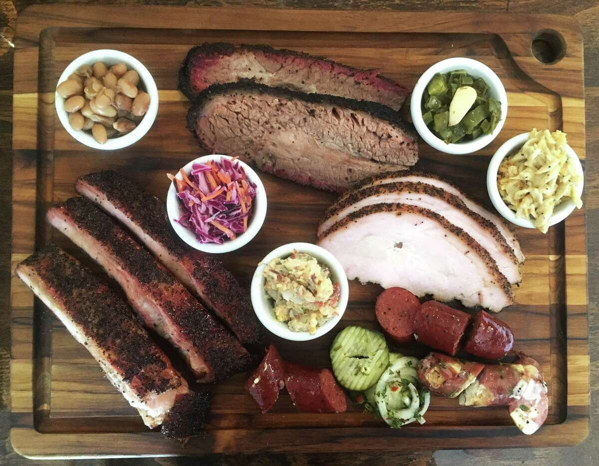 San Antonio's 2M Smokehouse board (from top left) includes: borracho beans, brisket, nopales, chicharoni macaroni, turkey, beef sausage link, pork serrano and Oaxacan link, house-made pickles and onions, potato salad, pork ribs and coleslaw.