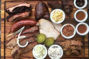 The Two Bros. BBQ Market board includes (from top left): cherry-glazed baby back pork ribs, chicken thigh, jalapeño poppers, creamed corn, beans, pulled pork, potato salad, smoked turkey, coleslaw, brisket and sausage.