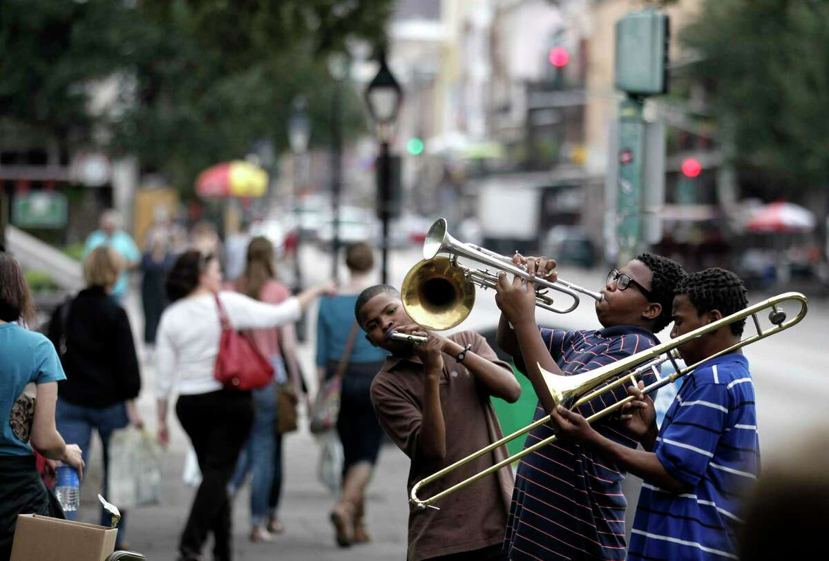FILE - In this Nov. 11, 2011 photo, Willie Andrews, Revert Andrews, 15, center, and Revon Andrews, 13, right, of the New Life Brass Band, perform in the French Quarter section of New Orleans. Mayor LaToya Cantrell says the city of Mardi Gras fame receives barely more than 1 in 10 of each dollar collected from the taxes and fees visitors pay.