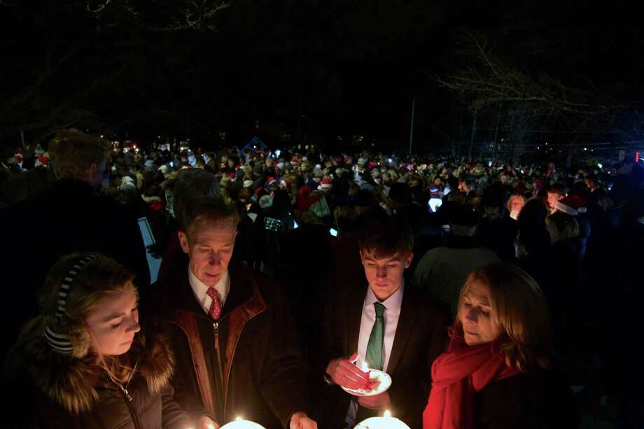 The Carlson family, of New Canaan, took part with hundreds of others at the annual community Christmas caroling at God's Acre on Monday in New Canaan. Photo: Jarret Liotta / For Hearst Connecticut Media / New Canaan News Freelance