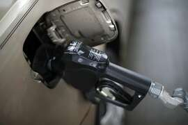 FILE - In this Nov. 16, 2018, file photo, a gas pump nozzle fills up gas in a car at a pump in West Mifflin, Pa. Expect prices to be relatively stable compared to this year, says Tom Kloza global head of energy analysis for the Oil Price Information Service. He said there is a good chance that 2019 will be book-ended by a very weak start for prices and a shaky finish _ with prices around $2.35 to $2.40 a gallon at each end. In between, prices will advance for both crude oil and gasoline.(AP Photo/Gene J. Puskar, File)