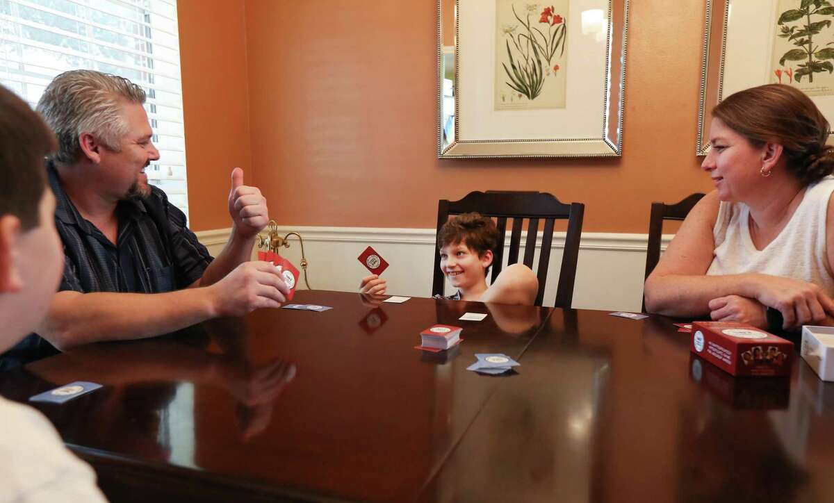 Brian Lindeen (second from left) gives his son, Zach, a thumbs-up as they play cards with brother, Quinn (left) and mother Piper Sunday, Dec. 2, 2018, in Sugar Land. The first FDA approved cannabis-based medication is available to U.S. patients through a prescription but its high cost, $32,500 a year, puts it out of reach of several patients. Some patients in Texas have opted to instead rely on the state's more affordable medical marijuana program, yet many patients remain locked out of the limited program.