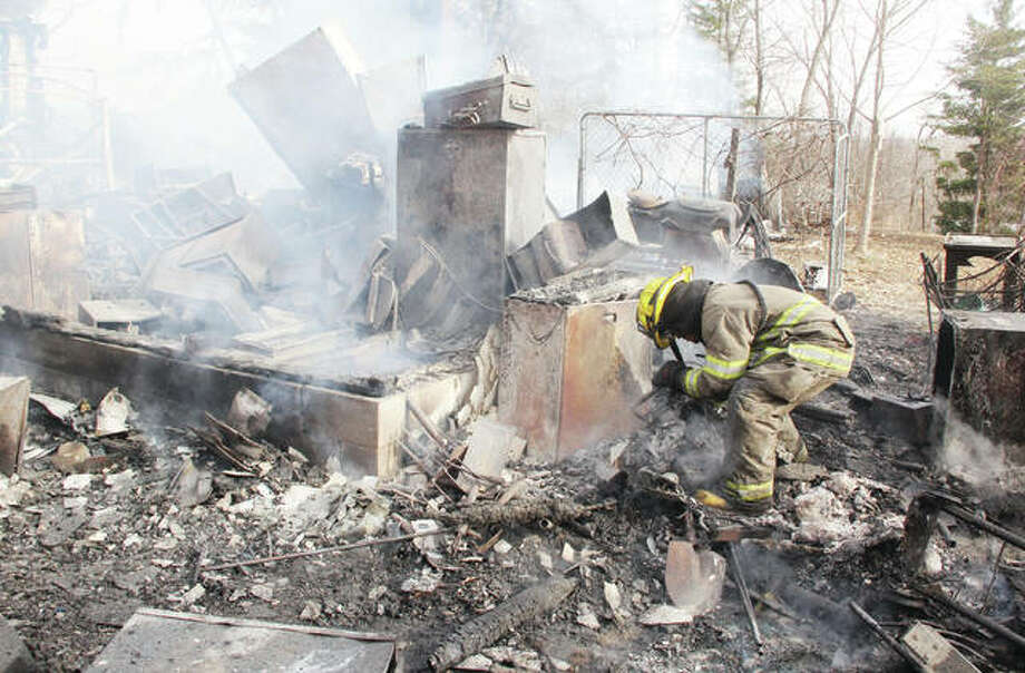 QEM firefighter Austin Darr looks over debris while searching for hot spots after fire destroyed a house and attached garage in the 27000 block of Beltrees Road. Photo: Scott Cousins   Hearst Illinois